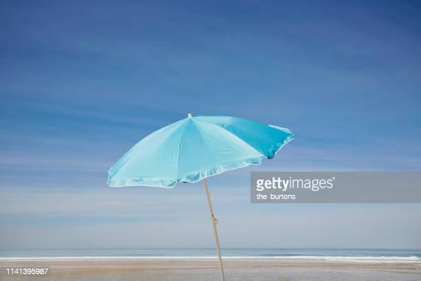 blue parasol on the beach against blue sky - parasol photos et images de collection