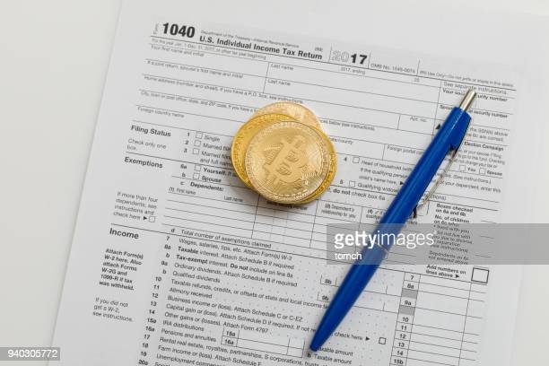 blue pen and bitcoins on the tax return - 1040 tax form stock photos and pictures