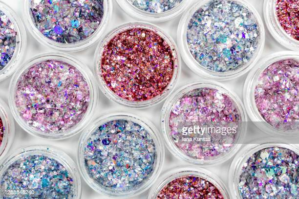 blue, pink and red glitter in jars on white background. shiny holographic elements, sparkle. beautiful shimmer for manicure, makeup, nail extension, design. cosmetic products. trendy delicate colors. - アイメイク ストックフォトと画像