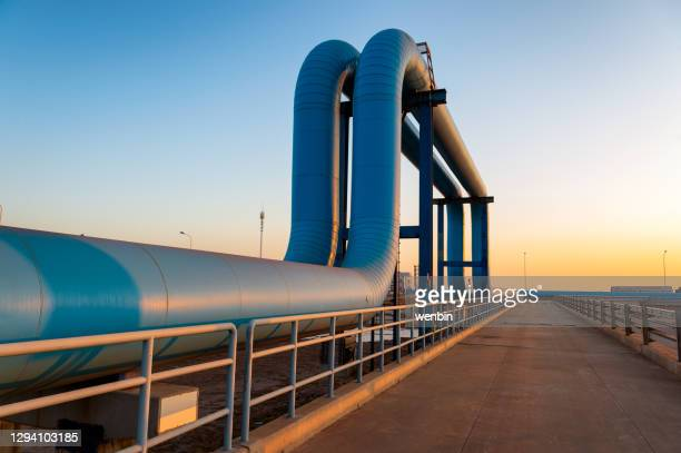 blue pipes going to oil refinery - industry stock pictures, royalty-free photos & images