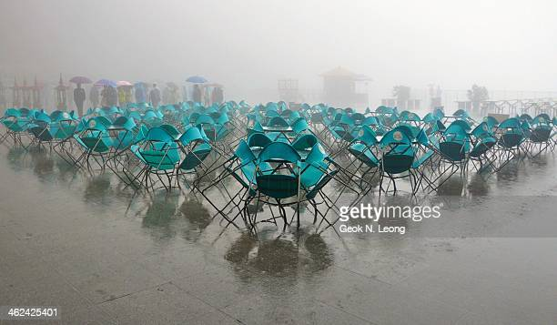 Blue plastic chairs against the tables in the rain, visual impact, perspective, triangle, shadows, wet, symmetry, reflections, atmospheric, people...