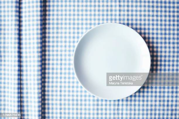 blue plate on a checkered blue-white fabric. - saucer stock pictures, royalty-free photos & images