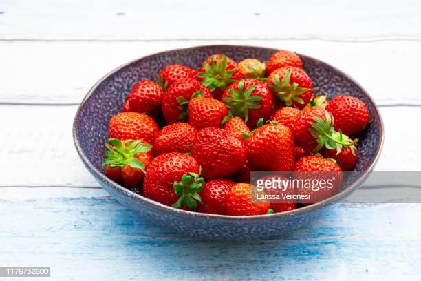 blue plate with strawberries on wood - larissa veronesi stock-fotos und bilder