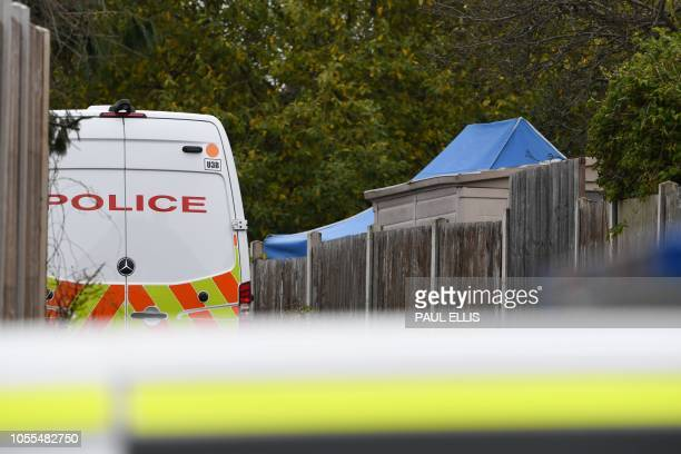 Blue police tent is visible above the fence in the back garden of a residential address being investigated by police in Sutton Coldfield, Birmingham,...
