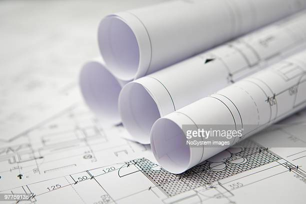 Blue prints on a table with rolled blueprints