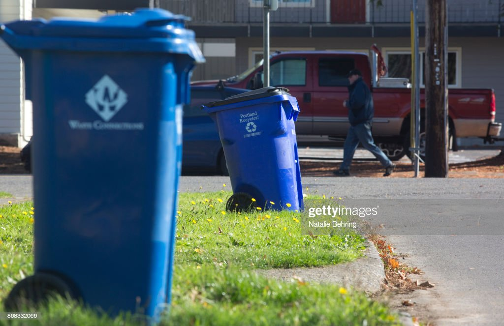 Blue recycling bins are seen on a residential street October 30, 2017 in Portland, Oregon. China is sharply restricting imports on recycled materials, and the impact will be felt across the Pacific Northwest. Some of the waste is likely to end up in the regions landfills as China rolls out new rules banning imports of 24 types of recyclables and restricting the amount of contamination in other imported waste materials.