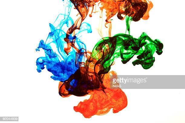 Blue, red and green ink dispersing in water