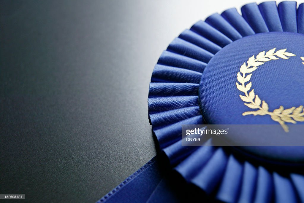 Blue ribbon rosette on dark gray graduated background : Stock Photo