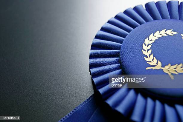 blue ribbon rosette on dark gray graduated background - award stock pictures, royalty-free photos & images