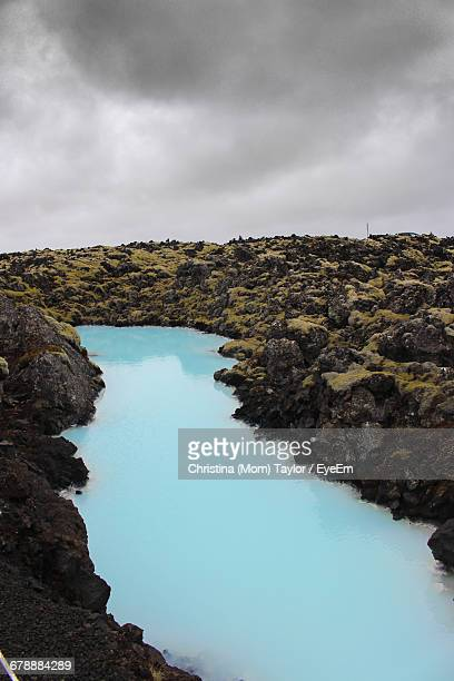 Blue River Amidst Rock Formations Against Cloudy Sky