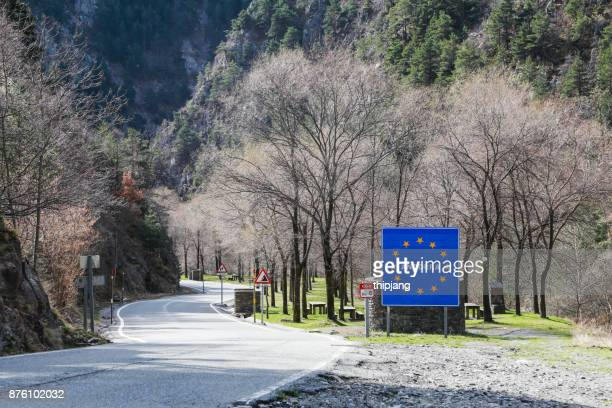 blue road sign with yellow stars in the border area between andorra and spain - andorra stock pictures, royalty-free photos & images
