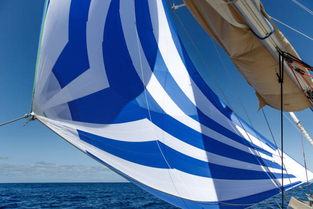 Blue sails fluttering over the white yacht