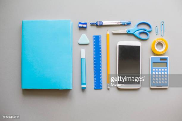 Blue school supplies on grey background