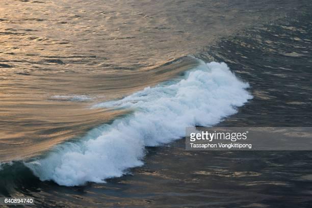 blue sea wave white spray splash orange sun light