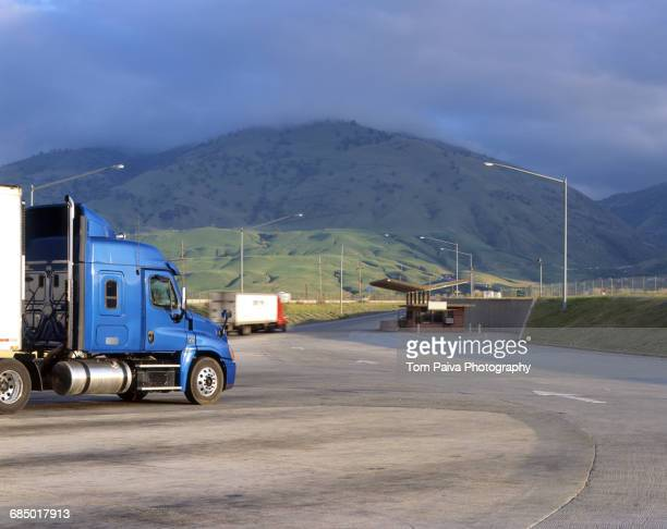 blue semi-truck following arrows on road - following arrows stock pictures, royalty-free photos & images