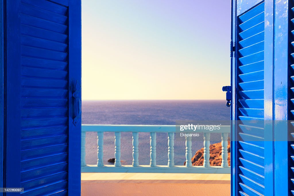 Blue Shutters Open onto Sea and Sky at Dawn : Stock Photo