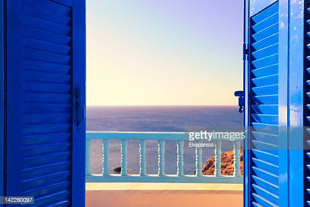blue shutters open onto sea and sky at dawn - shutter stock pictures, royalty-free photos & images