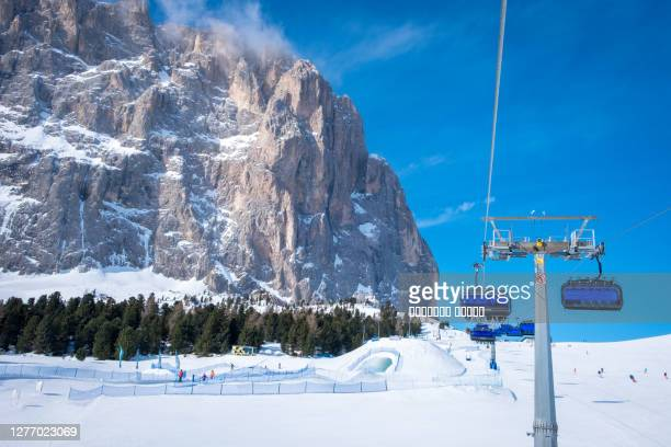 blue ski chairlift in ski resort of selva di val gardena, italy - european alps stock pictures, royalty-free photos & images
