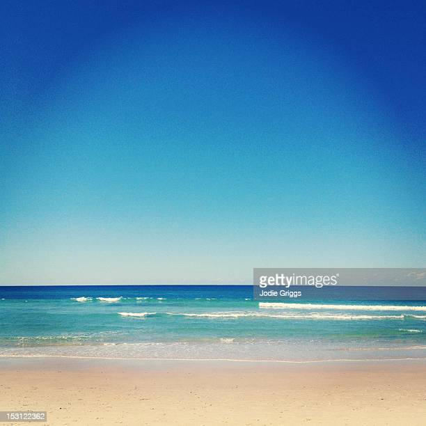 blue skies over aqua ocean waters at beach - water's edge stock pictures, royalty-free photos & images