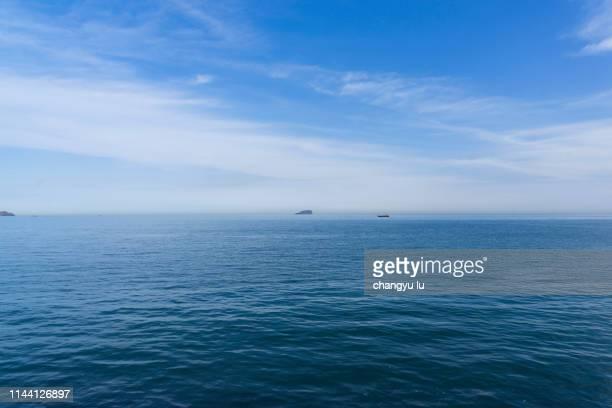blue sky and clear ocean; clouds in blue sky - alleen lucht stockfoto's en -beelden