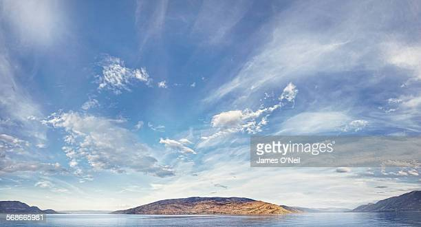 blue sky and clouds over water and land - 感動 ストックフォトと画像