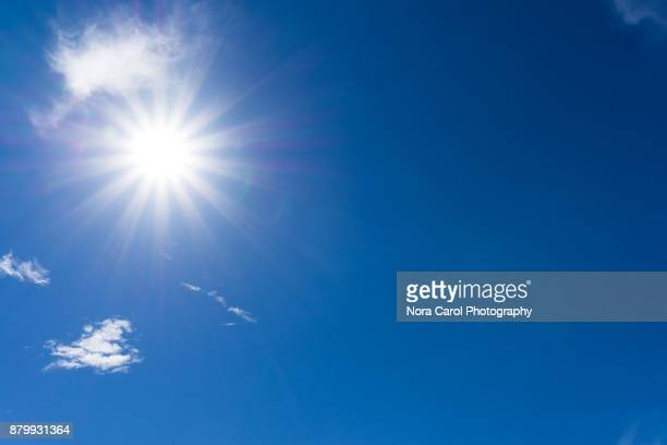 blue sky and clouds with sunburst - zonnestraal stockfoto's en -beelden