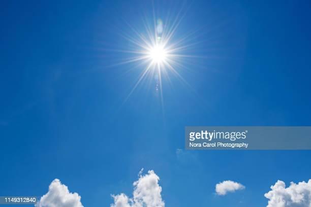 blue sky and sunburst - zonlicht stockfoto's en -beelden