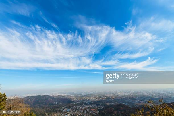 blue sky and white clouds over the city - vento foto e immagini stock