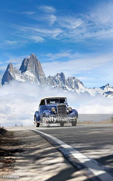 blue sky over antique car driving in patagonia argentina - hot rod car stock photos and pictures