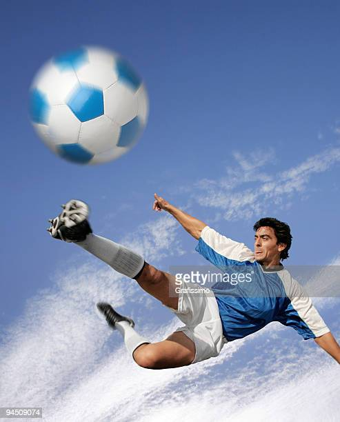 Blue sky over best soccer player hitting the ball