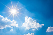 Blue sky with bright sun and clouds