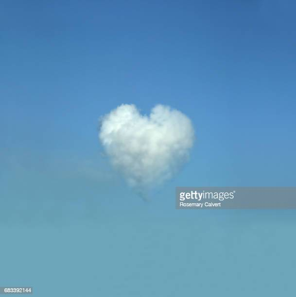 Blue sky with heart shaped white cloud.