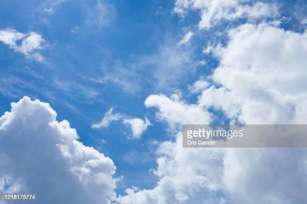 blue sky with white clouds background - cris cantón photography fotografías e imágenes de stock