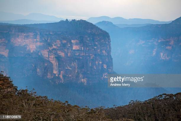 blue smoke from forest fire, bushfire in the grose valley with steep cliff face, escarpment at dusk, sunset, blue mountains, australia - great dividing range stock-fotos und bilder