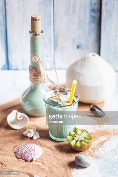 Blue Smoothie with coconut milk, banana, kiwi, spirulina, coffee coated coconut chips