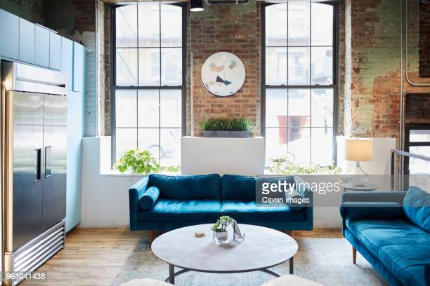 blue sofas and coffee table against windows in creative office on sunny day - tavolino foto e immagini stock