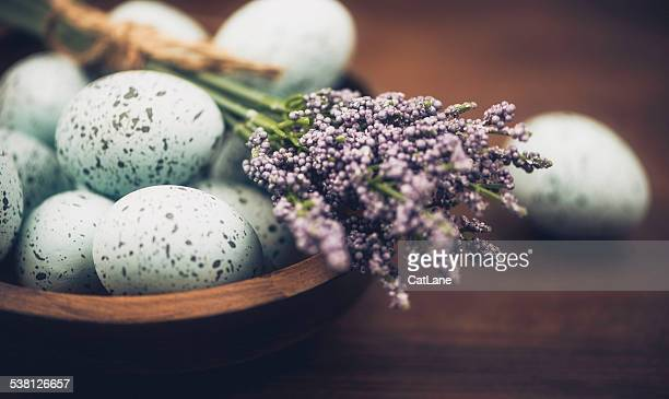 blue speckled eggs with rustic bowl and lavender. easter arrangement. - easter flowers stock pictures, royalty-free photos & images