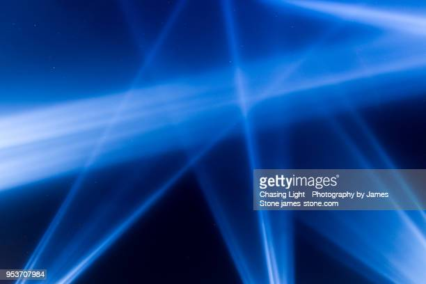 blue spotlights shining into a starry sky - spotlit stock pictures, royalty-free photos & images