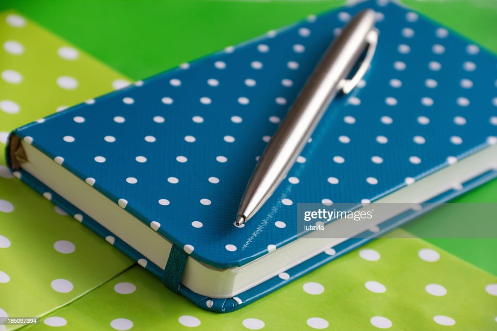 Blue spotted notebook and pen on green background : Stock Photo