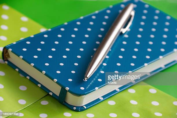 blue spotted notebook and pen on green background - lutavia stock pictures, royalty-free photos & images