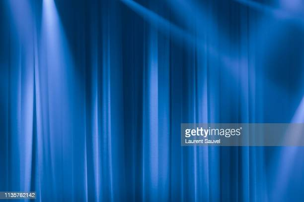 blue stage curtain in the spotlights with light rays - stage curtain stock pictures, royalty-free photos & images