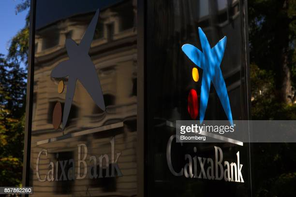 A blue star logo sits on display outside the headquaters of CaixaBank SA in Madrid Spain on Thursday Oct 5 2017 Catalan lenders such as CaixaBank SA...