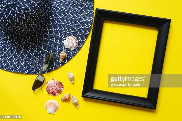 blue straw hat, seashells, sunglasses and picture frame - arts culture and entertainment stock pictures, royalty-free photos & images