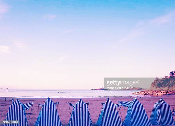 Blue Striped Tents On Sea Shore At Beach Against Clear Sky