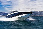 A blue striped white yacht speeding across the sea
