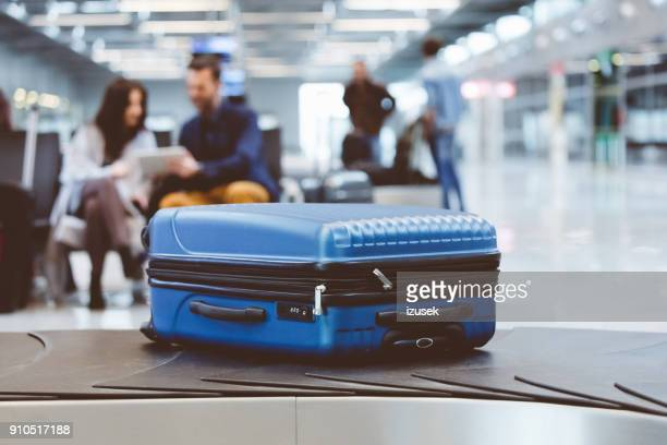 blue suitcase on conveyor belt at the airport with people in the background - baggage claim stock pictures, royalty-free photos & images