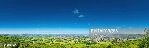 Blue summer skies over green patchwork landscape fields houses panorama