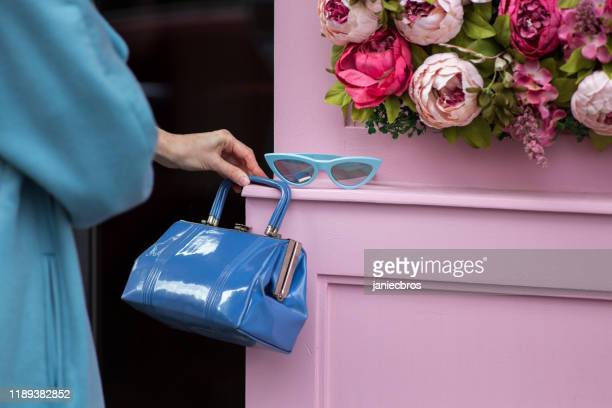 blue sunglasses and a purse against a pink wall - handbag stock pictures, royalty-free photos & images