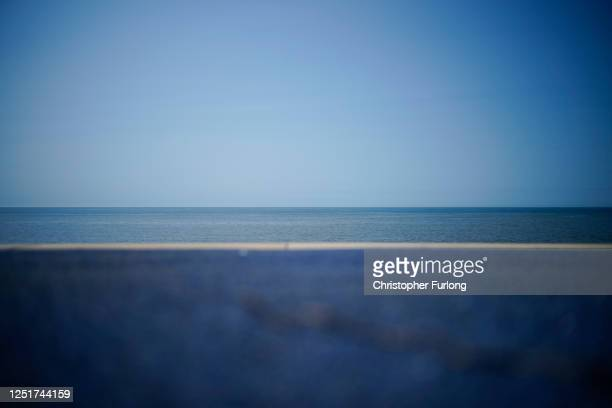 Blue tarmac meets the blue sea at Thornton Cleveleys promenade on June 24, 2020 in Blackpool, United Kingdom. The UK is experiencing a summer...