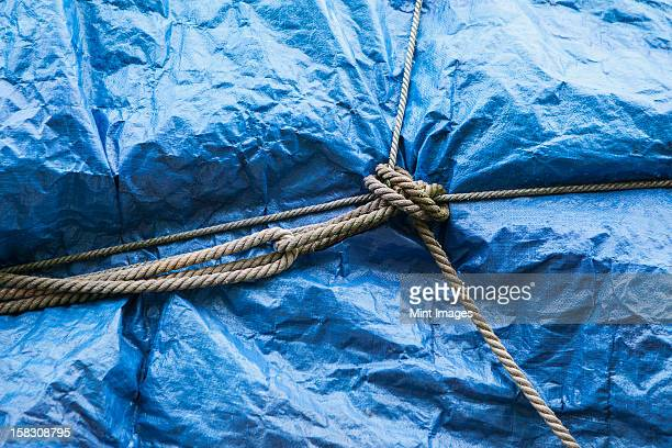a blue tarpaulin covering stacked commercial fishing nets on the dockside at fisherman's wharf, seattle.  - tarpaulin stock pictures, royalty-free photos & images